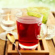 Glass of herbal tea on wooden table over bokeh background — Stock Photo #24037751