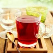 Glass of herbal tea on wooden table over bokeh background — Stock Photo
