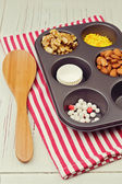 Cupcake ingredients in oven tray over red striped tablecloth — Stock Photo