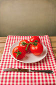 Tomatoes on red tablecloth over grunge background — Stok fotoğraf