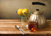 Vintage still life with teapot and lemons on wooden table — Stock Photo