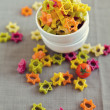 Colorful star pasta on textile background - Stockfoto