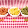 Pasta farfalle in bowls on red tablecloth — Stock Photo