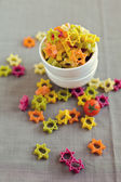 Colorful star pasta on textile background — Stockfoto