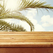 Empty wooden deck table over palm tree branches — Stock Photo