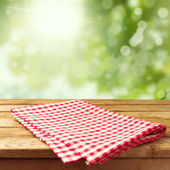 Empty wooden deck table with tablecloth — Стоковое фото