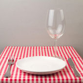 Setting with plate, silverware and wine glass — Stock Photo