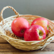 Royalty-Free Stock Photo: Red apples in basket on wooden deck table