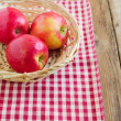 Red apples in basket on tablecloth — Stock Photo