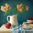 Still life with flowers and apple over blue background - Stock Photo
