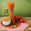 Italian pasta with tomatoes on striped tablecloth — Stock Photo