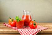 Tomato juice on wooden table — Stock Photo