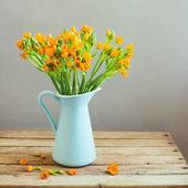 Fleurs oranges en pichet bleu sur la table en bois — Photo