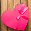 Heart shape gift box over wooden background — Stock Photo