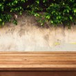 Wooden deck table over urban wall with leaves — Stock Photo