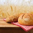 Fresh bread on tablecloth on wooden vintage table — Stock Photo #26183549