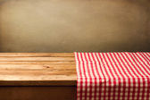 Empty wooden table covered with red checked tablecloth — Stock Photo