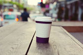 Paper coffee cup on wooden table over bokeh street — Stockfoto