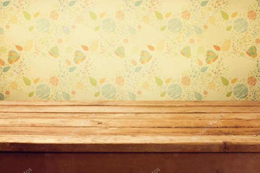 empty wooden deck table over floral print wallpaper