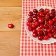 Cherries on plate with tablecloth on wooden background — Stock Photo