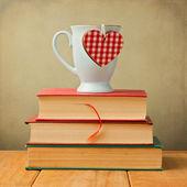 Coffee mug with heart shape on vintage books — Stock Photo
