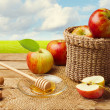 Apples with honey on wooden table over green meadow — Stock Photo