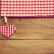 Retro toned background with checked tablecloth and heart shape on wooden board — Stock Photo