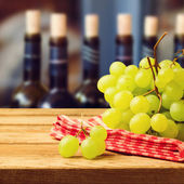 Grapes on tablecloth over wine bottles — Stock Photo