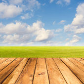 Wooden deck table over beautiful meadow with blue sky — Stock Photo