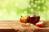 Honey and apples on wooden table over bokeh garden background — Stock Photo