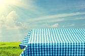 Empty table covered with blue checked tablecloth over beautiful sky. Ready for product montage — Stock Photo