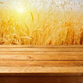 Empty wooden deck table over wheat field with sunset or sunrise. — Stock Photo