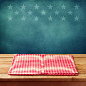 Empty wooden deck table with tablecloth for USA holidays background. — Stock Photo