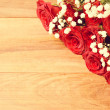 Wooden background with red roses — Stock Photo
