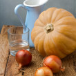 Still life with pumpkin and onions on wooden table — Stock Photo