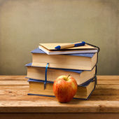 Stack of books with note book and apple. — Stock Photo