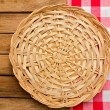Wicker plate on checked tablecloth — Stock Photo