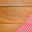 Background with wooden tabletop and checked tablecloth — Stock Photo