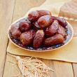 Dates on plate over wooden background — Stock Photo