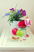Still life with apple, honey, pomegranate and flowers — Stock Photo