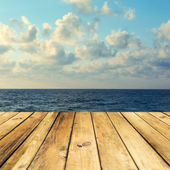Wooden deck floor over beautiful sea and sky background — Stock Photo
