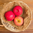 Apples in basket on wooden table — Stock Photo