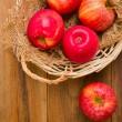 Fresh red apples in basket over wooden background — Stock Photo