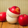 Red apple in stack of bowls on wooden table — Stock Photo #30701855