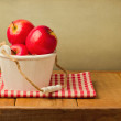Apples in wooden bucket on tablecloth — Stock Photo