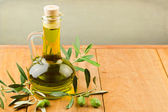 Olive oil on wooden table — Stock Photo
