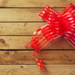 Wooden background with ribbon bow — Stockfoto