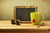 Tea cup, pines and chalkboard — Stock Photo