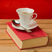 Coffee cup on vintage book — Stock Photo