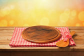 Round board on tablecloth on table — Stock Photo